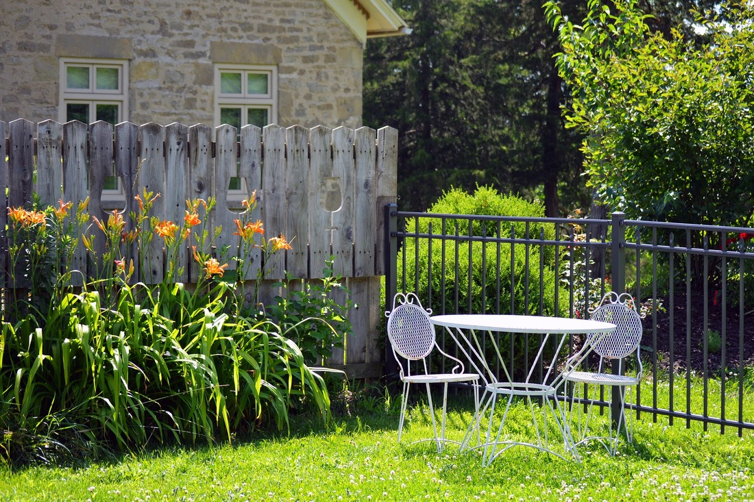 Yard setting with garden in the background and a table and two chairs